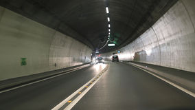 Road tunnel with cars. Light and projected shadows inside the Vedeggio-Cassarate road tunnel with lights,signs and traffic stock photography