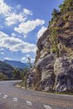 Road turn along steep rocky cliff. Sunny summer view with steep rocky cliff on the side of a road crossing the Siriu mountains in Buzau county, Romania Royalty Free Stock Image