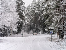 Road turn and leaving car in winter forest Royalty Free Stock Images