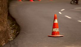 On the road with a turn, there is a warning cone with white stripes. royalty free stock images