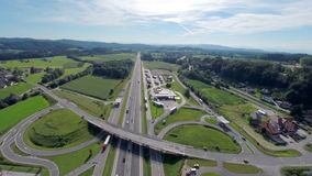Road turns exit from highway to a gas station. Aerial shoot of a road exit and turns to a gas station near a highway with cars and trucks on the road stock video footage