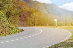 The road turns to the left among the small mountains and forests illuminated by the sun light. Road turns to the left among the small mountains and forests Stock Images