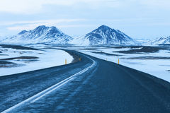 The road at  twilight through the snow capped mountains Stock Photo