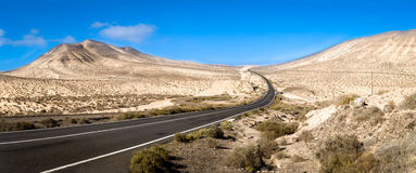 Road twisting through landscape. Road twisting through arid and sandy landscape Stock Photo