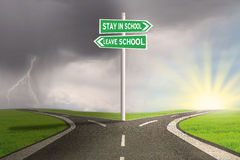 Road with two choices to stay or leave school. Image of empty highway with two choices on the signpost to stay or leave school Royalty Free Stock Image