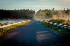 Road between two lakes in the misty sunris Royalty Free Stock Image