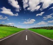 Road under beautiful sky between green hills Stock Photos