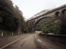 Road under a bridge inside the Pyrenees. A photo of a beautiful road in the Pyrenees.  this is on the side of France. The picture was taking real early in the Stock Image