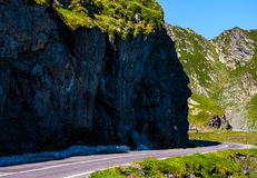 Road under the cliff in high mountains. Transportation background with dangerous aspect Royalty Free Stock Image