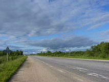The road under the clouds. Summer landscape with the straight road in Tverskaya region, Russia royalty free stock images