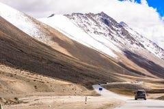 Road under snow berg. In Tibet, China Stock Photo