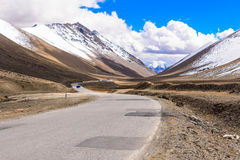 Road under snow berg. In Tibet, China Royalty Free Stock Images