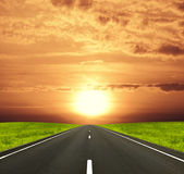Road under the sun. Road among green field and sunset sky Stock Images