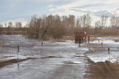 Road under water. Orange truck and people.  flood, inundation, windy sundy weather. spring. Siberia. Stock Photo