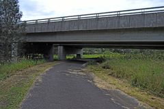Road underneath a highway bridge. Single lane road running underneath a bridge landscape stock images