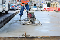 Road upgrade. CLUJ-NAPOCA, ROMANIA - CIRCA JULY 2014: Construction worker finishes concrete slab with trowel machine by road upgrade. Road segments are partially Stock Photo