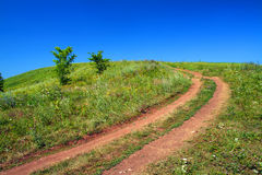 Road uphill. Rural road uphill on green field stock photo