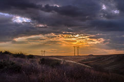 Road vanishing to the horizon under sun rays coming down trough the dramatic stormy clouds. Sunset at the mountain road. Azerbaija Stock Image