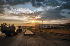 Road vanishing to the horizon under sun rays coming down trough the dramatic stormy clouds. Sunset at the mountain road. Azerbaija Royalty Free Stock Image