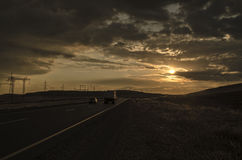 Road vanishing to the horizon under sun rays coming down trough the dramatic stormy clouds. Sunset at the mountain road. Azerbaija Stock Photo