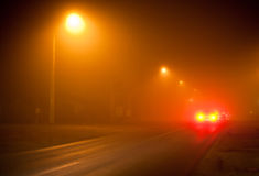 Road in a very foggy night. Road at night with extremely dense fog and yellow street lamps Stock Photography