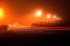 Road in a very foggy night. Extremely dense fog and yellow street lamps and car lights Royalty Free Stock Photo