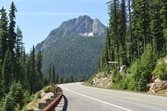 Road view along Highway 20, Washington State. Road view along Highway 20 in Washington state. Evergreen trees surround, with a mountain in the backgrround, under royalty free stock photography