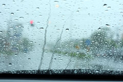 Road view through car window with rain drops Stock Photo