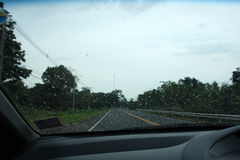 Road view through car window with rain drops.  stock image