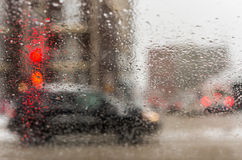 Road view through car window with rain drops and melting snow Royalty Free Stock Photo