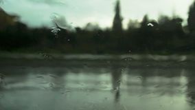 Road view through car windshield with rain drops. Waiting for cross the road stock video footage
