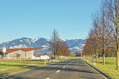 Road view of countryside and snow covered Swiss mountains Stock Photos