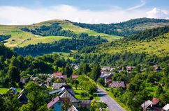 Road through village in Carpathian mountains. Bird eye view of beautiful rural scenery in summertime stock image