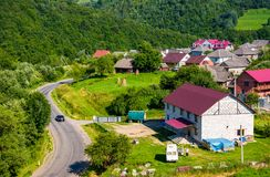 Road through village in Carpathian mountains. Bird eye view of beautiful rural scenery in summertime royalty free stock images