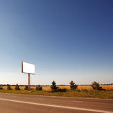 Road in a village with an empty billboard Royalty Free Stock Images
