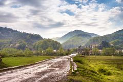 Road and village in green mountain valley Stock Photo