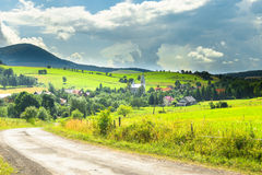 Road, village and mountain summer landscape Stock Photo