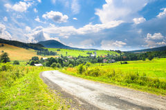 Road, village and mountain summer landscape Royalty Free Stock Image