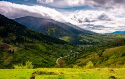 Road through the village in valley of Carpathians. Lovely springtime scenery in mountains of Synevyr National park Royalty Free Stock Images