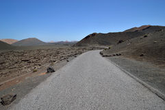 Road through the volcanic field. Road through the volcanic field, ash and rocks. Fire mountains - Montanas del Fuego, Lanzarote, Canary Islands, Spain stock image