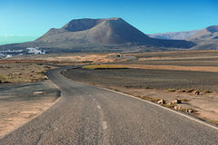 A road on volcanic landscape at  Lanzarote Island, Canary Island Royalty Free Stock Photo