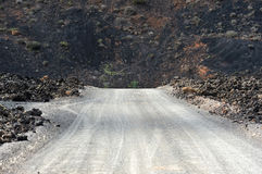 A road on volcanic landscape at  Lanzarote Island, Canary Island Royalty Free Stock Photos