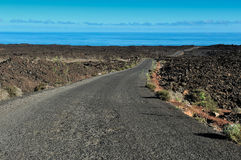 A road on volcanic landscape at  Lanzarote Island, Canary Island Royalty Free Stock Image