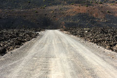 A road on volcanic landscape at  Lanzarote Island, Canary Island Royalty Free Stock Images