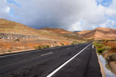Road in volcanic landscape, Lanzarote, Spain Stock Photos