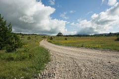 Road through the walley. Beautiful mountains landscape, macadam road, meadows and pastures Stock Images