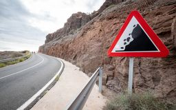 Road Warning sign: Falling Rocks. A triangular street sign giving warning of potential falling rocks and debris in the road royalty free stock images