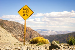 Road warning sign informing about rock slide area Royalty Free Stock Image