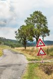 Road warning sign on slippery road. Spilled gravel on the road. Country road in the Czech Republic. Stock Images
