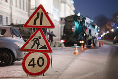 Road warning sign. workers work at night. Winter stock image